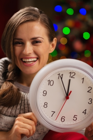 Portrait of smiling woman showing clock in front of Christmas lights photo