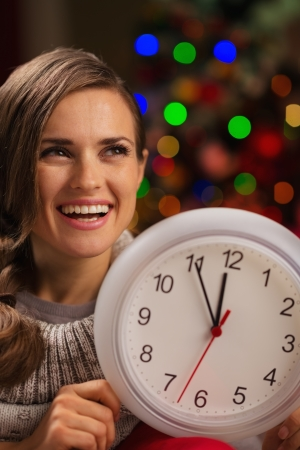 Portrait of happy woman showing clock in front of Christmas lights Stock Photo - 16192530