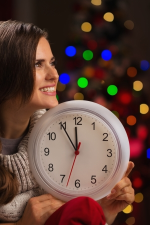 Portrait of happy woman showing clock in front of Christmas lights Stock Photo - 16192509