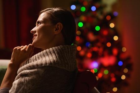 donna seduta sedia: Donna pensosa seduta sedia di fronte di albero di Natale Archivio Fotografico