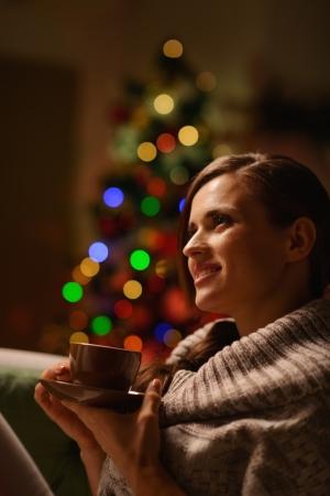 donna seduta sedia: Donna pensosa seduta sedia e bere bevande calde di fronte di albero di Natale
