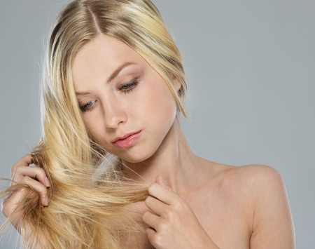Portrait of blond girl checking hair ends Stock Photo - 16305091