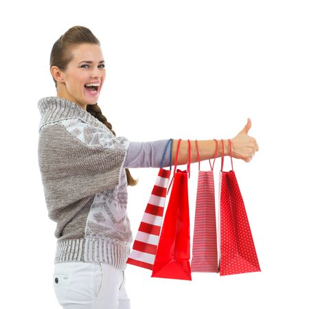 Happy woman in sweater showing thumbs up with shopping bags Stock Photo - 16336924