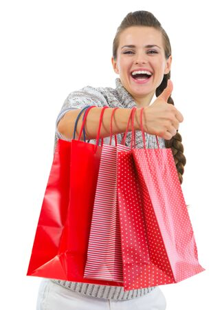 Smiling woman in sweater showing thumbs up with shopping bags Stock Photo - 16336946