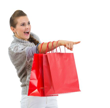 Happy woman in sweater with shopping bags pointing on copy space Stock Photo - 16336919