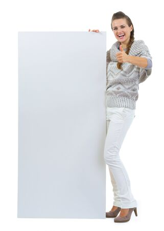 Happy woman in sweater holding blank billboard and showing thumbs up Stock Photo - 16336928