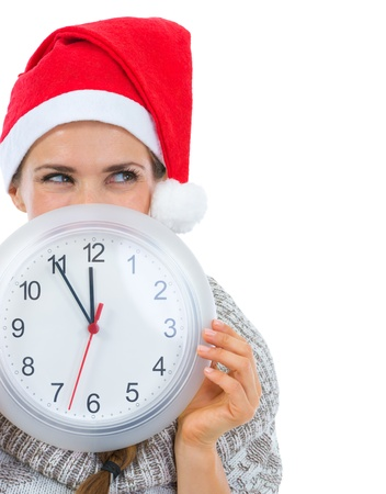 Woman in Santa hat holding clock in front of face and looking on copy space Stock Photo - 16336927