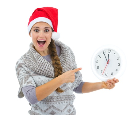 Surprised woman in Santa hat pointing on clock Stock Photo - 16336926