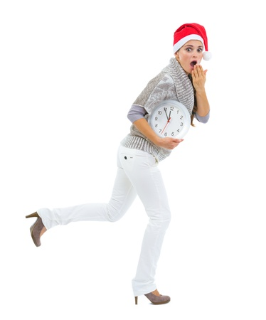 holiday tradition: Shocked woman in Santa hat holding clock and running