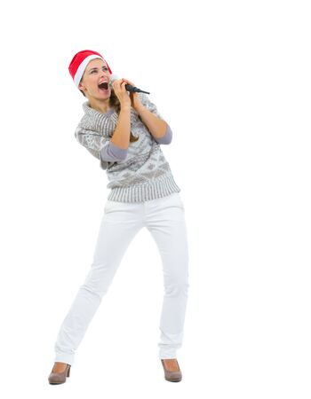 Happy woman in Santa hat singing in microphone and looking on copy space photo