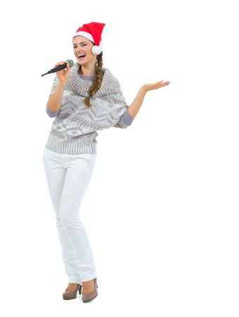 Smiling woman in Santa hat with microphone presenting something Stock Photo - 16336914