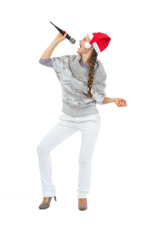 Happy woman in Santa hat singing in microphone photo