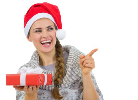 Woman in Santa hat holding Christmas gift and pointing on copy space Stock Photo - 16336947