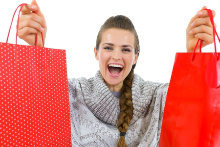 discounting: Happy woman in sweater showing red shopping bags