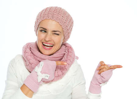 Smiling woman in knit winter clothes pointing on copy space and winking Stock Photo - 16467284