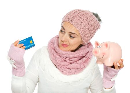 Confused woman in knit winter clothing holding credit card and piggy bank Stock Photo - 16467275