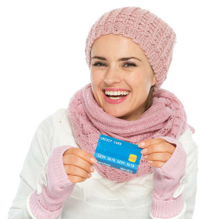 Smiling woman in knit scarf, hat and mittens holding credit card Stock Photo - 16467307