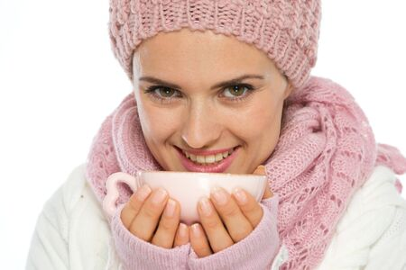 Smiling young woman in knit winter clothing holding cup of hot tea photo