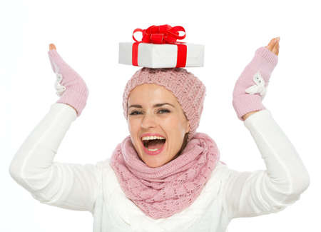 Happy woman in knit winter clothing balancing Christmas present box on head Stock Photo - 16467290
