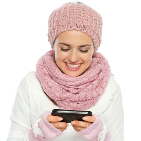 Smiling woman in knit winter clothing writing text message Stock Photo - 16467308