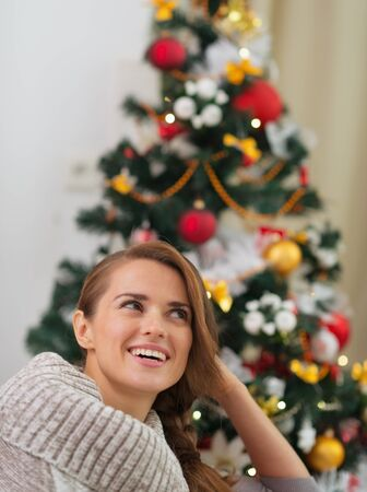 Dreaming woman in sweater sitting in front of Christmas tree Stock Photo - 16467316