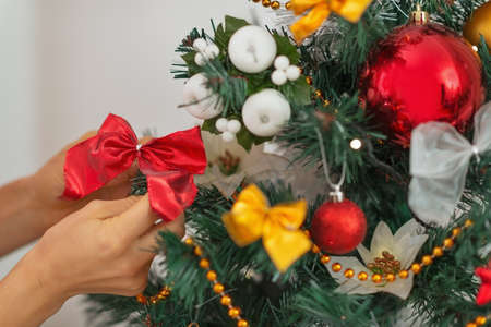 Closeup on woman hand decorating Christmas tree Stock Photo - 16478375
