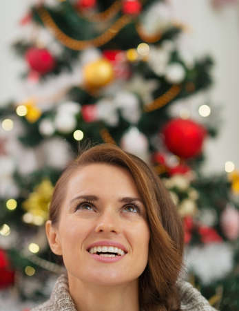 Woman in front of Christmas tree looking up Stock Photo - 16467256