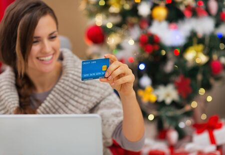 Closeup on credit card in hand of happy woman with laptop near Christmas tree Stock Photo - 16467239