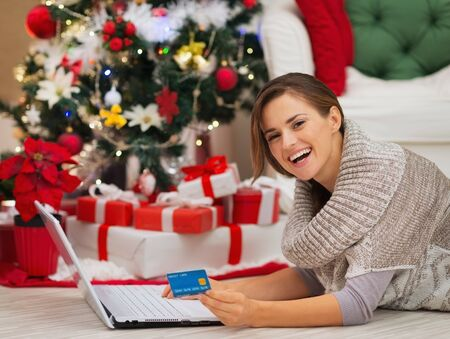 Happy woman with laptop near Christmas tree making online purchases Stock Photo - 16467224