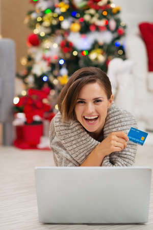 Smiling woman with laptop and credit card near Christmas tree Stock Photo - 16467267