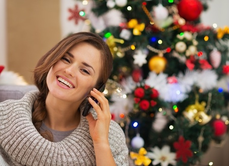 Happy woman near Christmas tree making phone call Stock Photo - 16467229