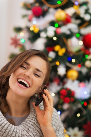 Smiling woman near Christmas tree making phone call Stock Photo - 16467225