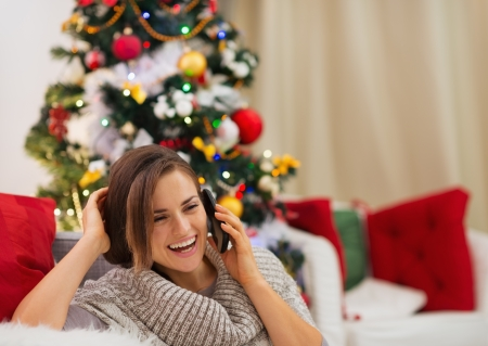 Happy woman near Christmas tree speaking mobile Stock Photo - 16467245