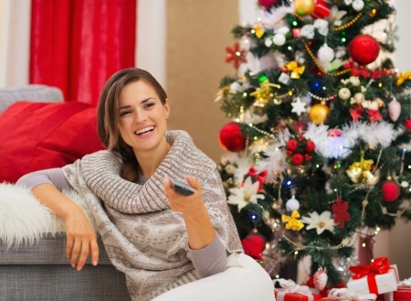 Happy woman watching TV near Christmas tree Stock Photo