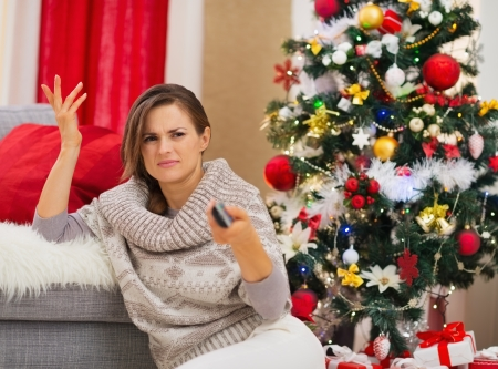 Frustrated woman with TV remote control near Christmas tree photo