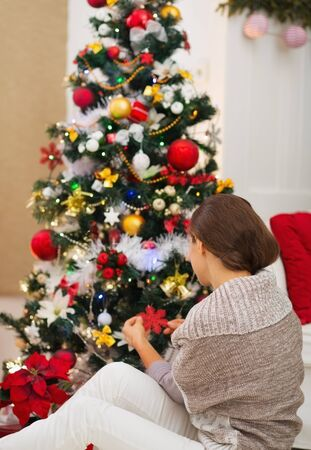 decorating christmas tree: Woman sitting near and decorating Christmas tree. Rear view