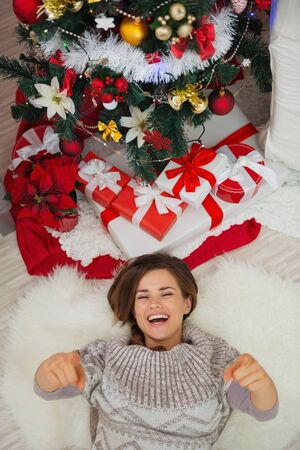 Happy woman laying near Christmas tree and pointing in camera photo