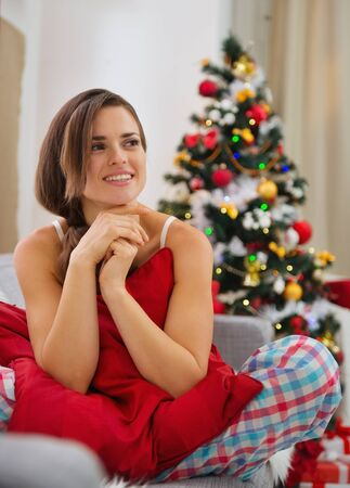 Happy woman sitting on divan in front of Christmas tree Stock Photo - 16467246