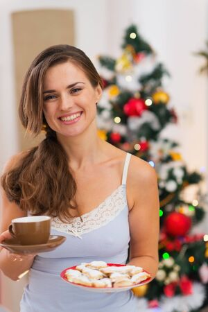 Happy woman in pajamas holding hot beverage and cookies in front of Christmas tree photo