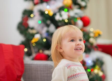 baby near christmas tree: Portrait of baby near Christmas tree