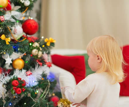 Baby decorating Christmas tree. Rear view Stock Photo - 16577984