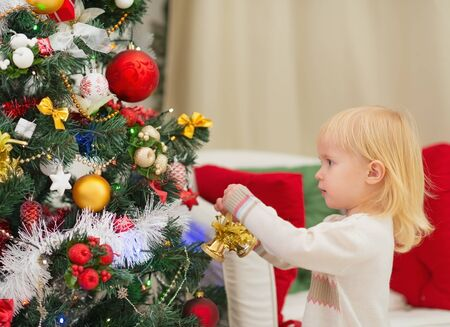 Baby decorating Christmas tree Stock Photo - 16577991