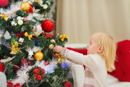 Baby girl decorating Christmas tree Stock Photo - 16578022