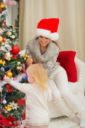 Mother looking on baby decorating Christmas tree photo