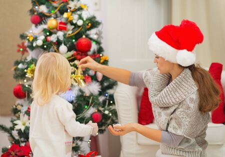 decorating christmas tree: Mother and baby decorating Christmas tree