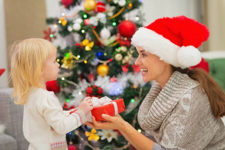 Baby girl presenting mother Christmas gift Stock Photo - 16578020