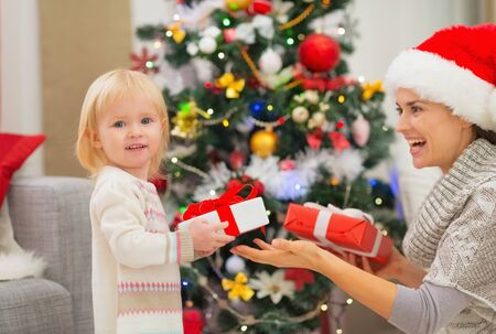 Mother and baby girl changing Christmas presents Stock Photo - 16578017