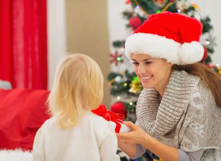 Mother presenting baby girl Christmas present Stock Photo - 16577985