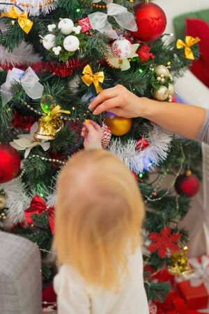Baby decorating Christmas tree. Rear view Stock Photo - 16578021