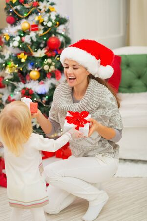 Mom and baby girl changing Christmas presents Stock Photo - 16578006